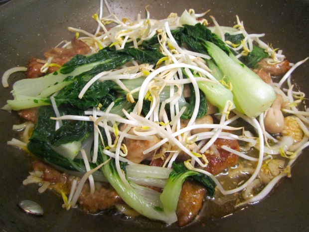 Add blanched bok choy and bean sprouts, saute until heated through.