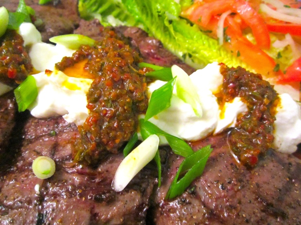 arrange salad and steaks on serving platter, top steaks with spicy chimichurri and greek yoghurt