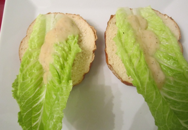 cut 2 bretzel rolls in half, reserve 2 top parts, top with romaine leaf and garlic aioli