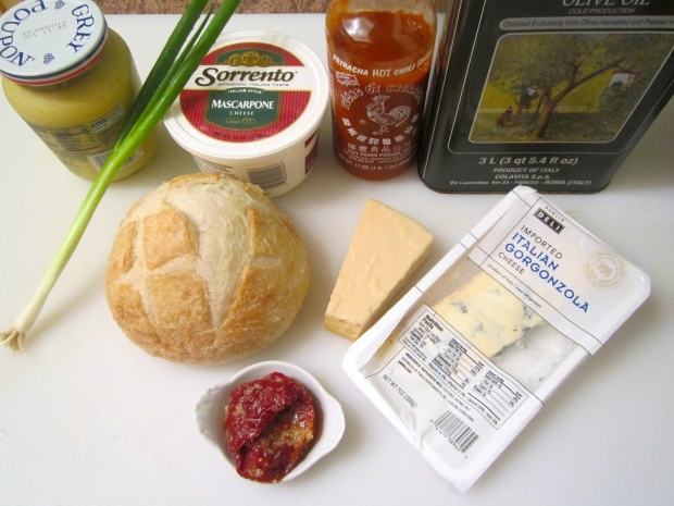 mise en place: Sour dough loaf, sun dried tomato, sliced chives, sliced asiago cheese, crumled gorgonzola, mustard, sriracha, olive oil