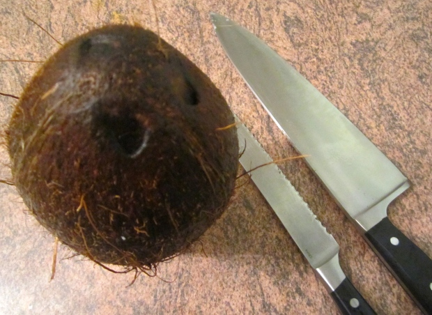 to split the coconut, saw a small inision around the outside of the coco, then crack it with the back of a large chefsknife or machete (I live in Florida where it is normal to have a machete in the house) :-)