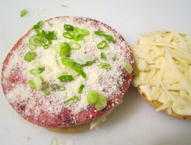 top first bread with ham, sprinkle with grated cheese and scallions or herbs of your choice