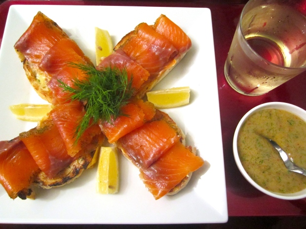 top with thinly sliced gravlax, serve with dill/ mustard sauce, lemon slices and chilled white wine