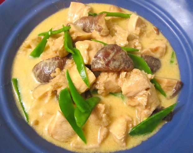 ladle soup with chicken and shiitake on top of pasta and snow peas