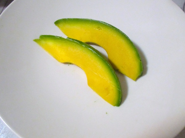 add two generous slices of avocado to hot serving plate