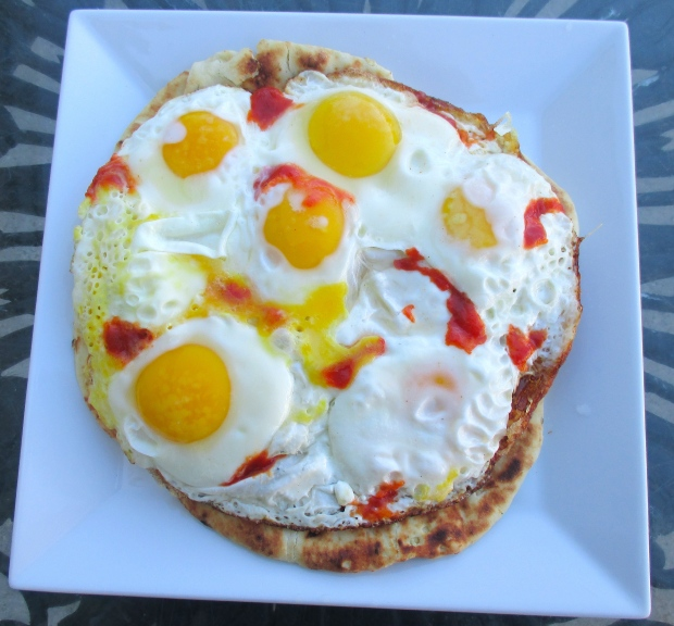 top naan with fried eggs, drizzle with sriracha