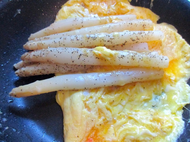 make an omelette with four whole eggs, seasoned with kosher salt and cayenne pepper, fold asparagus into omelette