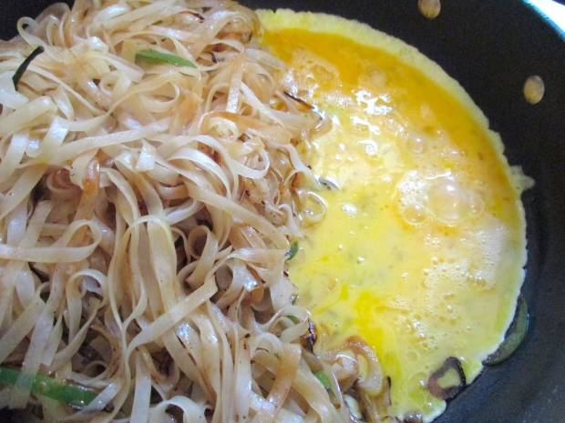 put noodles to one side of the pan, add some more garlic oil, add whisked eggs, scramble, cook until eggs are dry