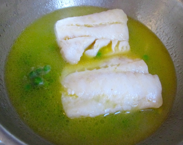 add blanched green peas to the poaching liquid of the fish, let heat through for another minute