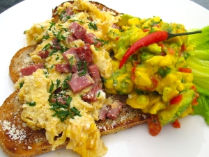 top other half of bread with scrambled eggs, sprinkle with finely crumbled queso blanco and sliced chives