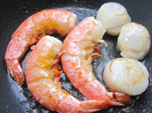 season scallops and shrimp with kosher salt and cayenne pepper, saute in garlic oil, remove from heat