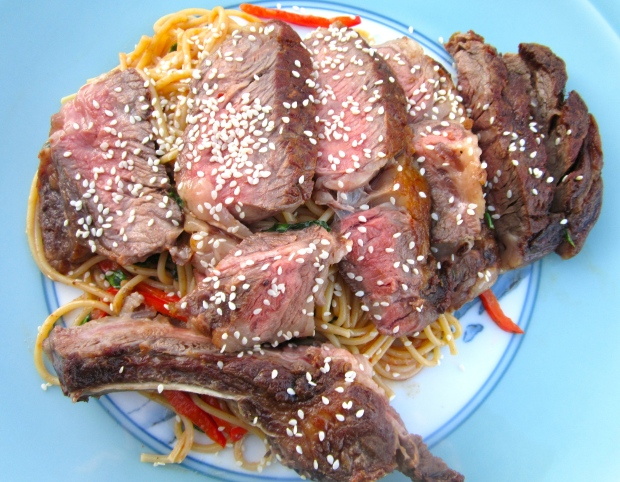 top pasta with sliced steak, sprinkle with sesame seeds