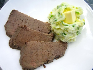 to serve, place a portion of potatoes on plate next to sliced corned beef, make an indention, place a generous knob of butter in indention