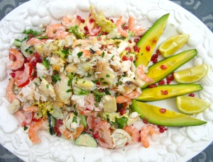 sprinkle salad with pomegranate seeds, top with crab meat and shrimp, drizzle with fresh lemon juice