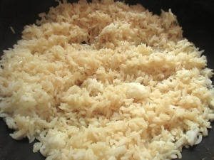 add day-old cooked rice to oil, stir fry until rice makes popping sound