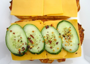 top both slices of bread with sharp cheddar, then top one slice with sliced cucumbers , season with kosher salt and chili flakes