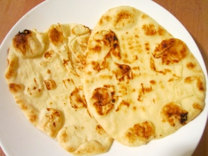 Brush hot naan with butter, sprinkle with kosher salt