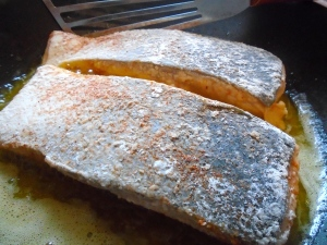 season salmon fillets with kosher salt and cayenne pepper, dust in flour