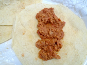 spread a generous amount of re-fried beans on tortilla