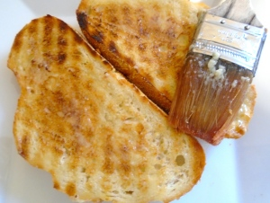 grill a thick slice of sour dough bread, brush with garlic-confit paste (not original, but oh so yummy)