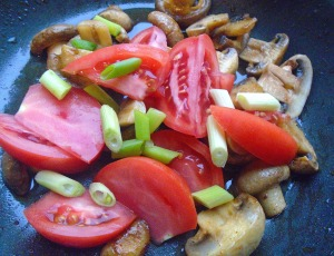 add tomatoes ans scallions, season with kosher salt and cayenne pepper, saute until heated