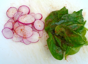 season fresh spinach leaves and thinly sliced radish with kosher salt and cayenne pepper