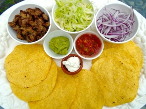 serve fried tortillas with sauted chorizo, shredded iceberg, salsa mexicana, guacamole, sour cream and finely sliced red onions
