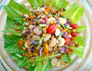 add octopus salad, drizzle dressing from octopus salad all over romaine leaves, sprinkle with honey roasted corn kernels for crunch and additional flavor