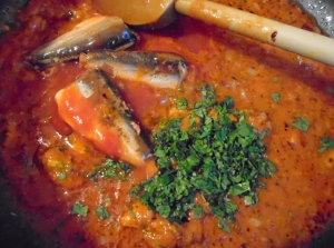 add canned sardines in tomato sauce (reserve 3 filets per portion), add chopped italian parsley and chopped oregano (or dry oregano), simmer until sardines are heated through and break into chunks