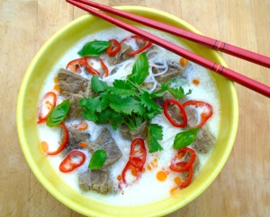 top with finely sliced chili, cilantro and young basil leaves