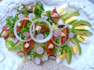 add sliced, salted  radishes, egg, avocado and onion rings, top each piece of fish with grated horseradish, drizzle a bit of dressing over avocado and egg