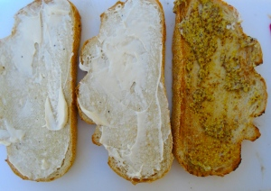 spread mayo on the un-toasted sides of the 2 slices bread which were toasted on one side only; spread mustard on both sides of the bread with was toasted on both sides