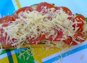 add the tomato slices, sprinkle with grated cheese