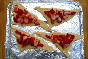 unroll the dough and divide into it's 8 pre-cut triangles, place 4 of the triangles on a foil-lined, dry baking sheet (no grease), top ea triangle with 1/3 cup frseh strawberries