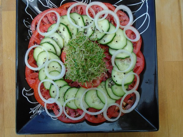 slice 2 large, very ripe tomatoes and 1 medium size white onion into fine slices, arrange on serving platter, sprinkle with sea salt and fresh-cracked black pepper to taste, add 1/2 tray alfalfa sprouts, drizzle with 3 tblsp white balsamic vinegar and 3 tblsp olive oil