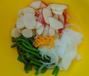 core and slice 1 ea red apple into fine slices, add two packed cups of fresh-cooked green beans, 2 cups cooked, sliced potatoes, 1 medium size sliced onion and 1 finely sliced yellow medium-hot chili
