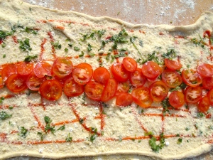 cut tomatoes in half, add into the center-line of the dough, season with kosher salt and granulated garlic to taste